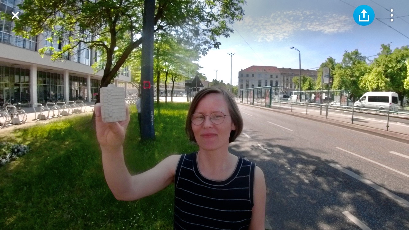 """Frauke Röth mit einem kleinen Betonmodell des """"Haus des Reisens"""" in Potsdam."""